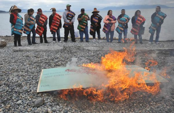 "Members of the Lummi Nation protest the proposed coal export terminal at Cherry Point by burning a large check stamped ""Non-Negotiable."" The tribe says they want to protect the natural and cultural heritage of the site. Read more at http://indiancountrytodaymedianetwork.com/article/northwest-tribes-step-up-opposition-to-proposed-coal-terminals."